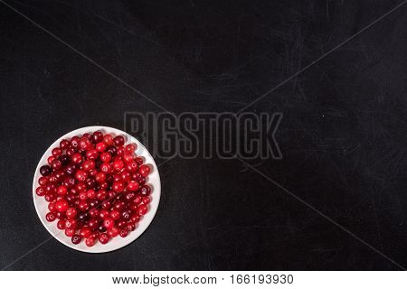 Cranberry. Cranberries On White Plate  Dars Stone Background
