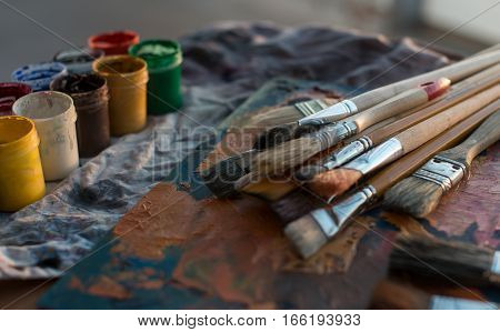 Photo of gouache and watercolor with brushes set in art studio. Oil paints smeared on palette.