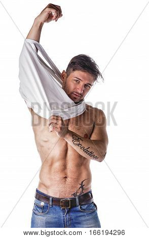 Handsome muscular young man taking off t-shirt, isolated on white, looking at camera
