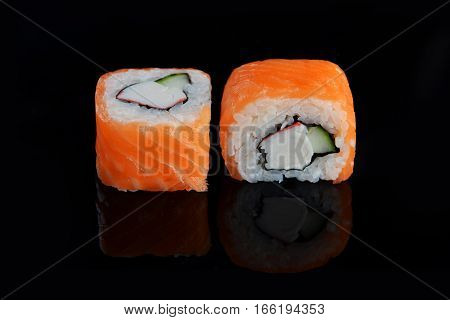 two sushi with salmon on black background
