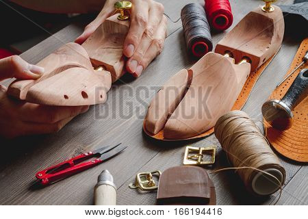 cobbler tools in workshop on dark background close up with hands