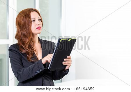 Young businesswoman in modern bright office holding the tablet with a list of tasks. Free space for text. Business concept of office work