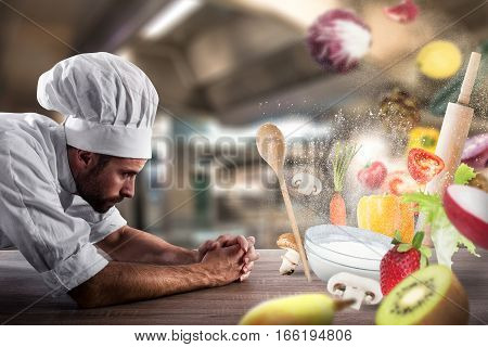 Chef with hat and apron looks on the table ingredients mingle with each other