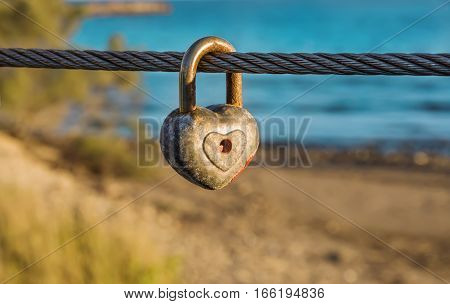 Old rusty heart shaped padlock with peeled off red paint in enlarged view as symbol of eternal love hanging on bridge metal cable in front of beach. Romance concept. Blurred background.