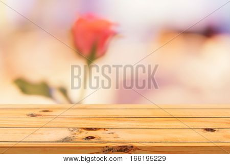 Wooden board empty table blurred background. Perspective brown wood over blur flower vase in coffee shop - can be used for display or montage your products. Mock up for display of product.