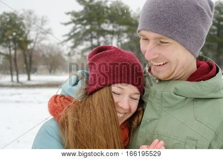 Happy Young Couple having fun in Winter Park. Family Outdoor. people season love and leisure concept