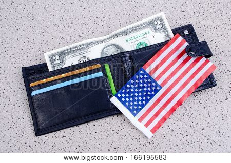 Banknote two dollars black purse and an American flag. On a gray background.