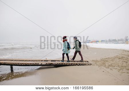 young Couple on winter beach. young woman and a man walking along a wooden jetty