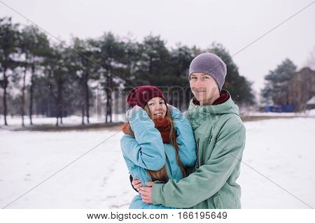 Happy couple playful together during winter holidays vacation outside in snow park. young man and woman hugging outdoor