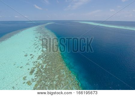Aerial view of a tropical island in turquoise water maldives for holiday vacation background concept -Boost up color Processing.