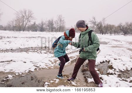 young woman and a man pass a puddle during the spring snow melt