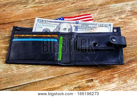 One hundred dollars in the wallet and the American flag. On a wooden surface.