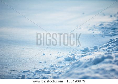 Textured surface of the snow-covered field. Winter high contrast background.