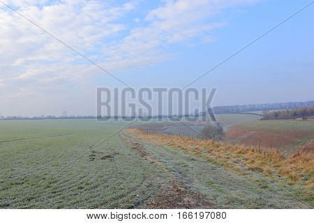 A frosty English landscape in winter with farmland, woods and valleys of the scenic Yorkshire wolds countryside in January