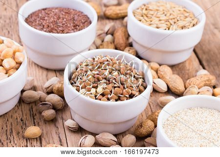 Bowls of various legumes and seeds. Lentils, sesame seeds, pistachio nuts, flaxseed, peanuts and chickpeas. Sprouted legumes. Wooden background