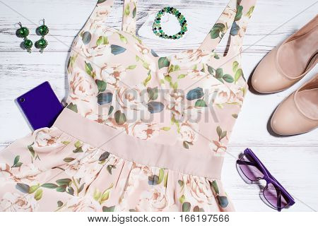 Woman summer clothes collection - chiffon floral skater dress, beige high heels, green jewellery, violet sunglasses and smartphone on a wooden background