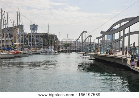 BARCELONA SPAIN - SEPTEMBER 2016: Couples and families with children sitting on pier at Rambla and Port Vell. People having rest dining and watching cruise yachts. Aquarium Barcelona and funicular.