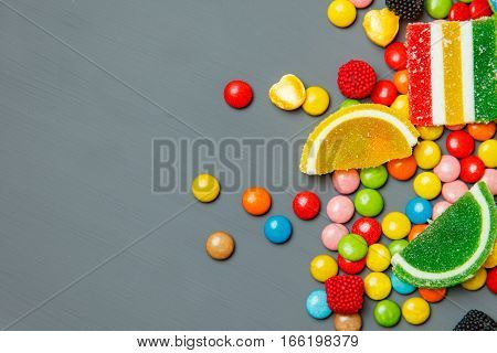 Mixed colorful fruit bonbon close up on gray background