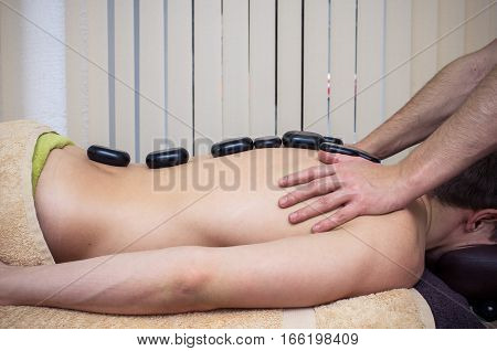 Photo of the man's hands, making massage of the back with the stones