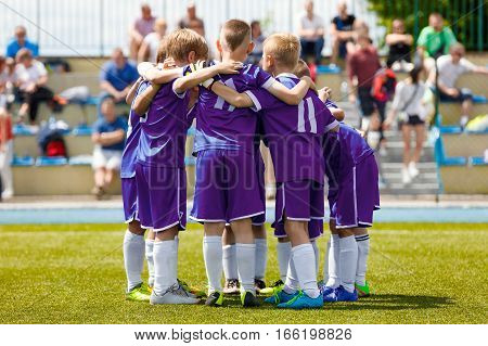 Children's Football Team on the Pitch. Boys in Purple Soccer Jersey Shirts Standing Together on the Football Field. Motivated Young Soccer Players Before the Final Game of School Tournament