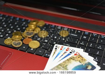Abstract idea of playing online poker. Laptop with some playing cards.