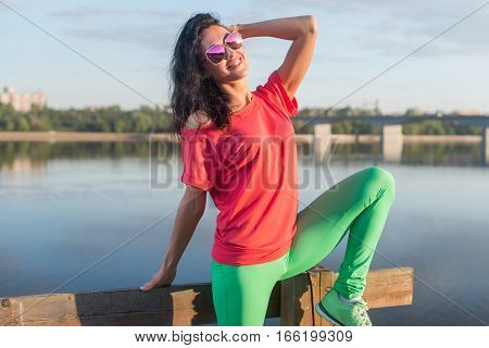 Smiling summer woman wearing sunglasses near river