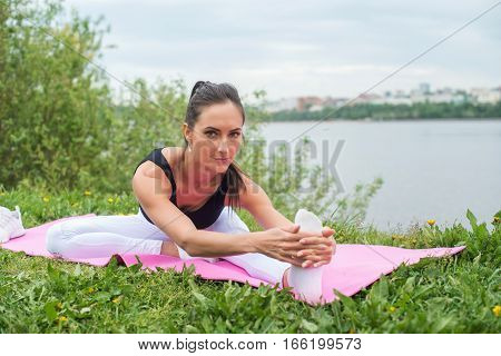 Athletic woman stretching her hamstring, legs exercise training fitness before workout outside on a beach
