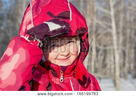 child in the bright jacket in the winter plays