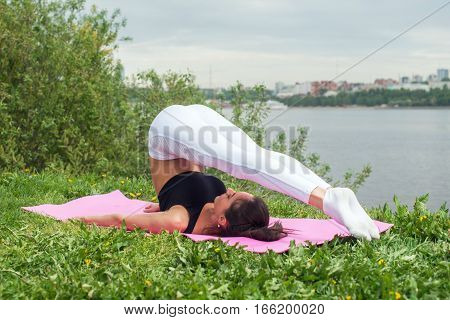 Fit woman making yoga in plow pose on mat in nature