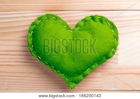 Green heart on natural wooden table on Valentine's Day. Pantone greenery color theme.
