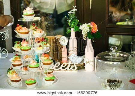 The cakes on the banquet and vases with flowers