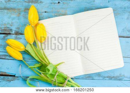 Tulips And Notebook On Blue Table