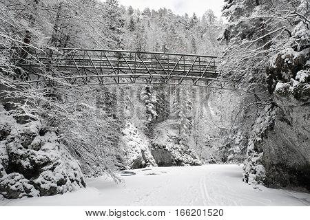 Empty bridge over frozen river Hornad in Slovak paradise. Wintertime