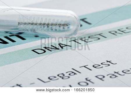 Buccal swab in test tube on paternity DNA test result chart form