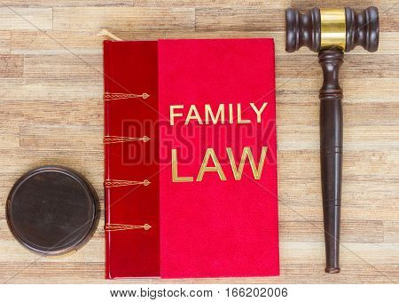 Wooden Law Gavel and red legal Family Law book on wooden table desktop, top view