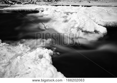 Long exposure water. River in snowy forest. Black and white art photography