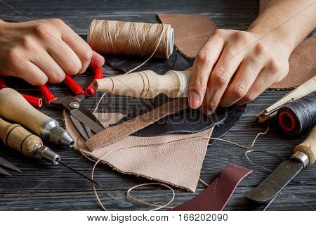 work in leather shop on dark wooden background close up with hands