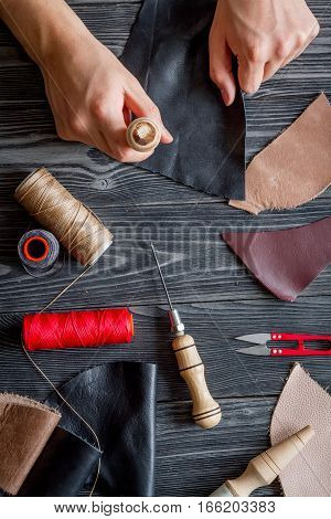 work in leather shop on dark wooden background top view with hands