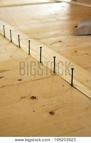 Installation of the floor in a house. Screws lined up before tightening. Diagonal view closeup