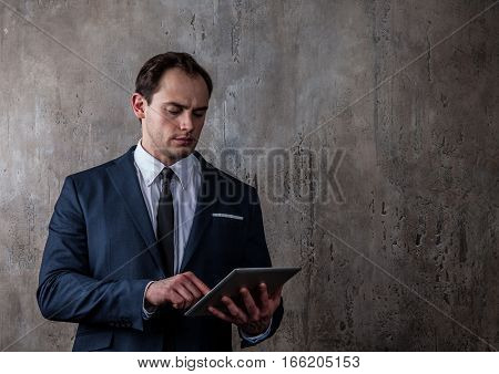 Portrait of a mature businessman with tablet in a suit on concrete gray wall background
