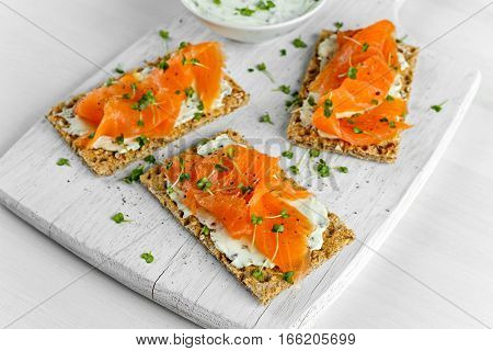 Homemade Crispbread toast with Smoked Salmon, Melted Cheese and cress salad. on white wooden board.