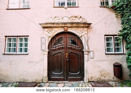 Riga, Latvia. Old Wooden Brown Door Of The Portal, Decorated By Molding On Facade Of Ancient Building On Torna Street In Old Town In Summer Day.