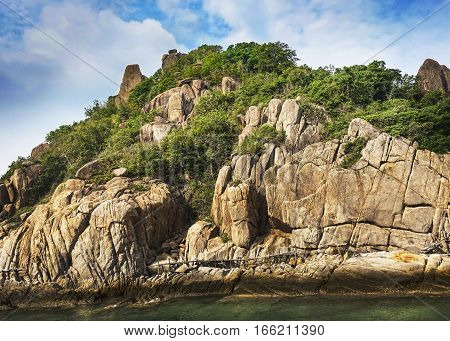 Green Island of Koh Tao in Thailand With Green Flora Covering Massive Stones souranded by turquise water