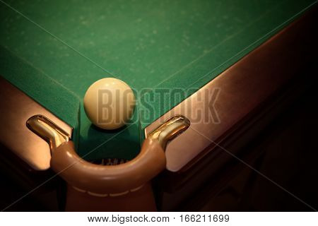Ball for russian billiards on green table near with hole, vignette
