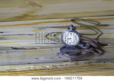 Vintage watch pocket and a bunch of rusty old keys on wooden background with a copy space