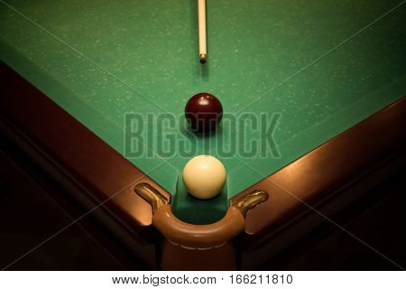 Balls and cue for russian billiards on green table near with hole, vignette