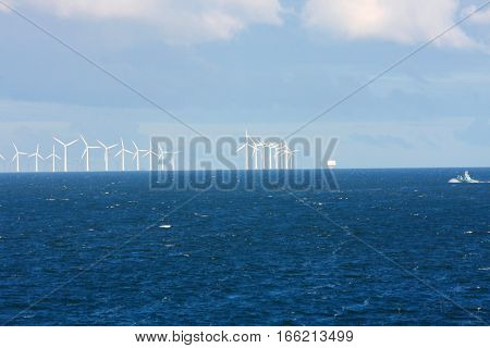 Perspective line of ocean wind mills with dark water and sky