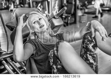 Athletic woman portrait in sportswear, squatting and pushing to train her legs on the leg press machine in her gym. Healthy lifestyle concept. Close up view. Shot in black and white.