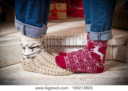 Close photo of the couple's feet in cute socks standing one on another