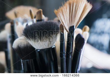 Makeup brushes in tube. Dirty makeup tools.